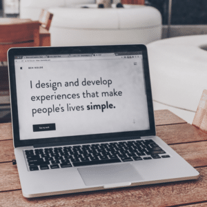 """Open laptop sitting on a table with text on screen """"I design and develop experiences that make people's lives simple."""""""