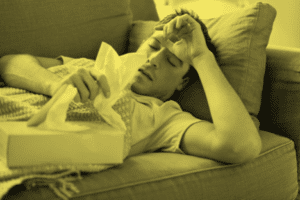 Person with cold/flu lying on sofa with tissues